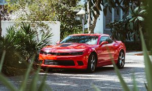 red camaro on a tropical street
